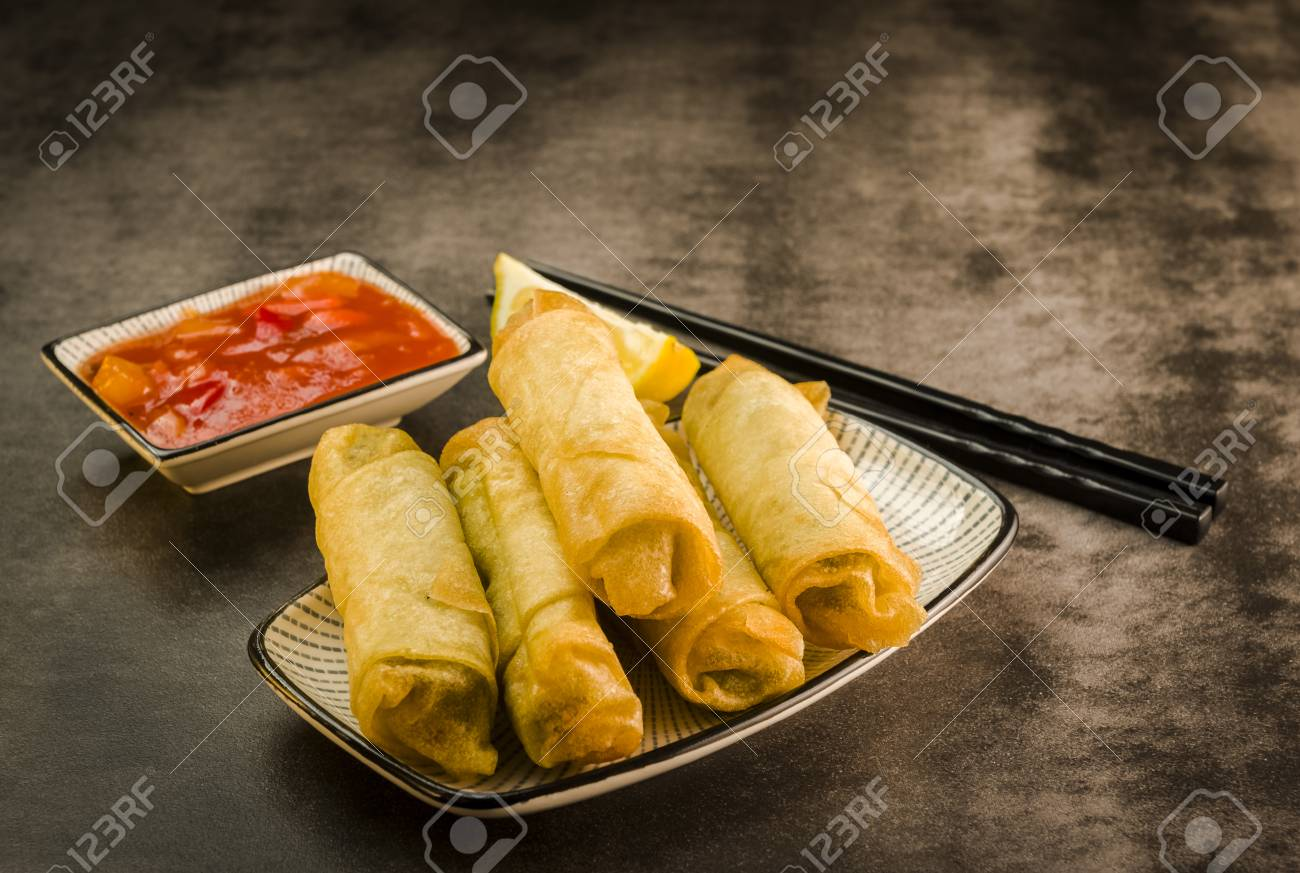 Spring rolls with vegetables, chopsticks and sweet and sour sauce - 87655415