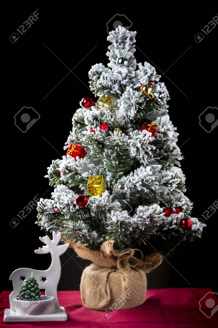 Small Christmas tree and Christmas decorations on a wooden table