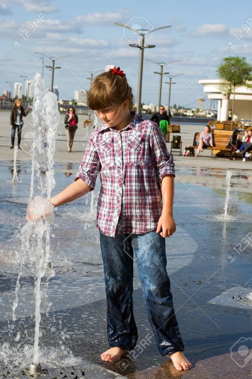 19d648c89f Foto de archivo - Niña de 8 años en pantalones vaqueros mojados y la camisa  que juega en la fuente en el parque de verano