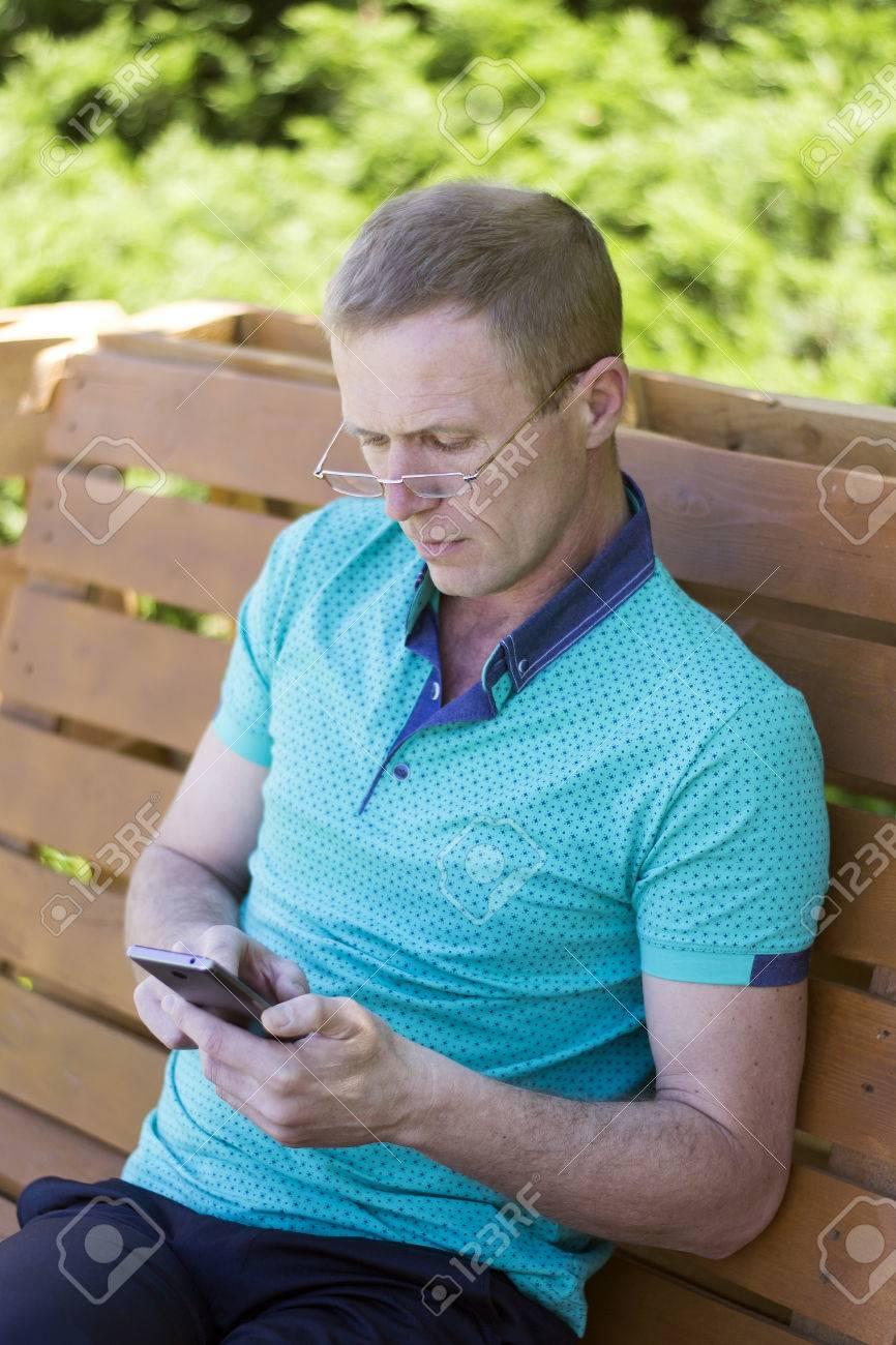 06aef827740c8f Banque d images - Homme d âge moyen portant des lunettes sur le nez, gros  plan, lisant un message sur un téléphone intelligent assis sur un banc dans  un ...