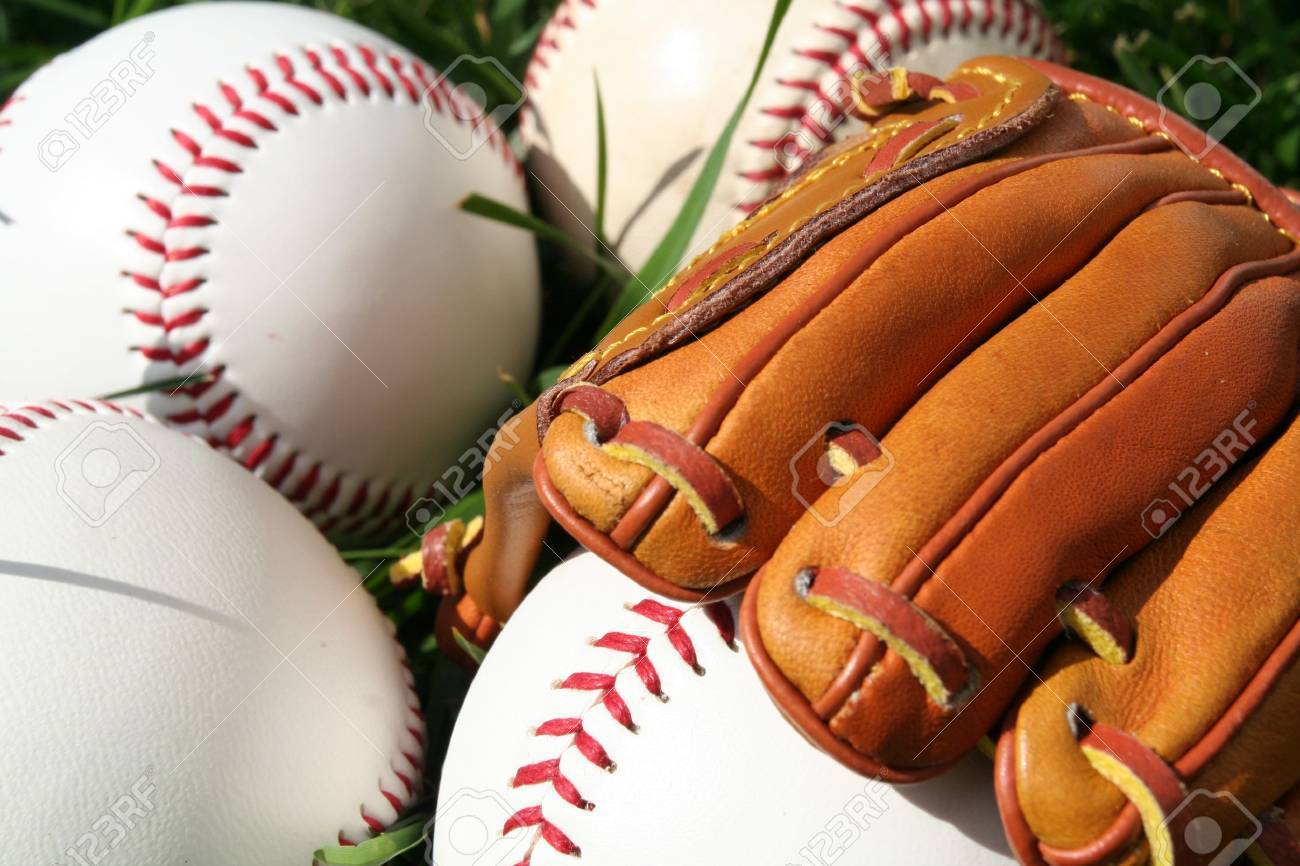 A baseball glove surrounded by balls on a field Stock Photo - 13142313
