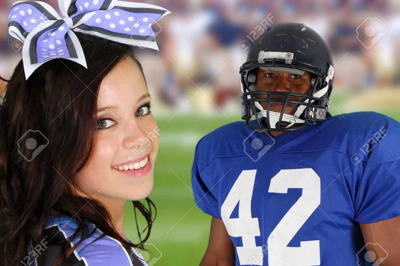 Teenage cheerleader with a football player on the field Stock Photo - 14747690
