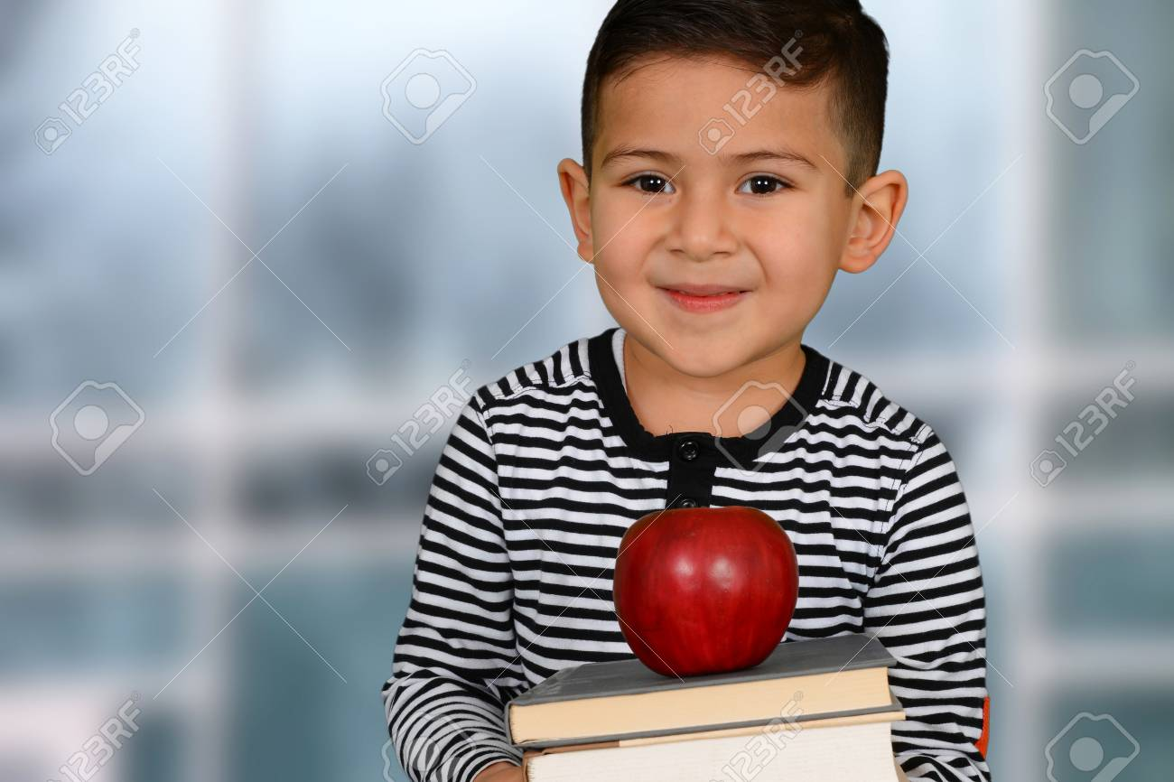 e4b1f8514344 Happy little schoolboy posing with red apple Stock Photo - 38730539