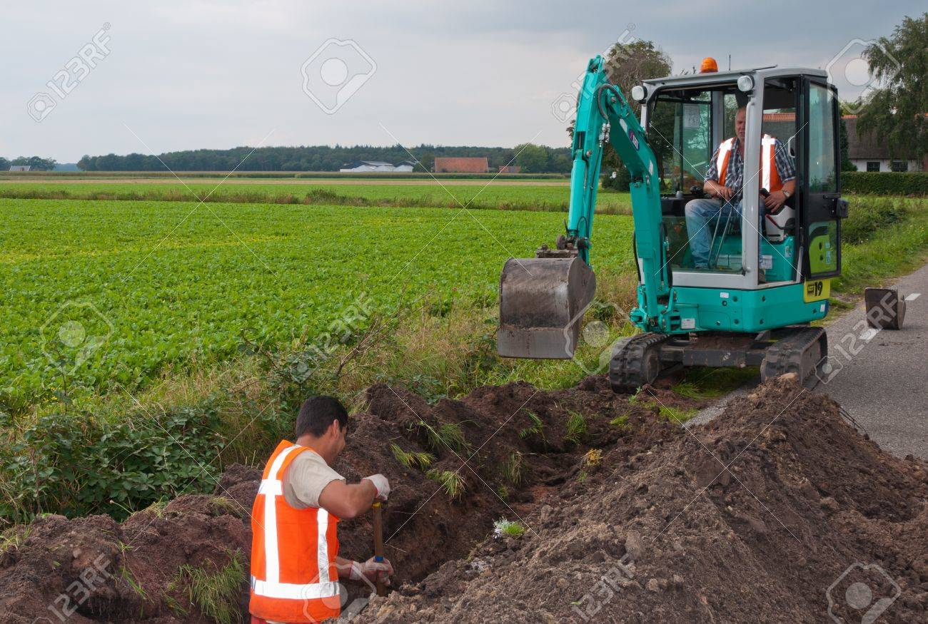 Ground engineering works in the Netherlands. Man and mini excavator dig a trench to lay cables in the village of Wouw, North-Brabant, Netherlands on September 15, 2011. Stock Photo - 10592100