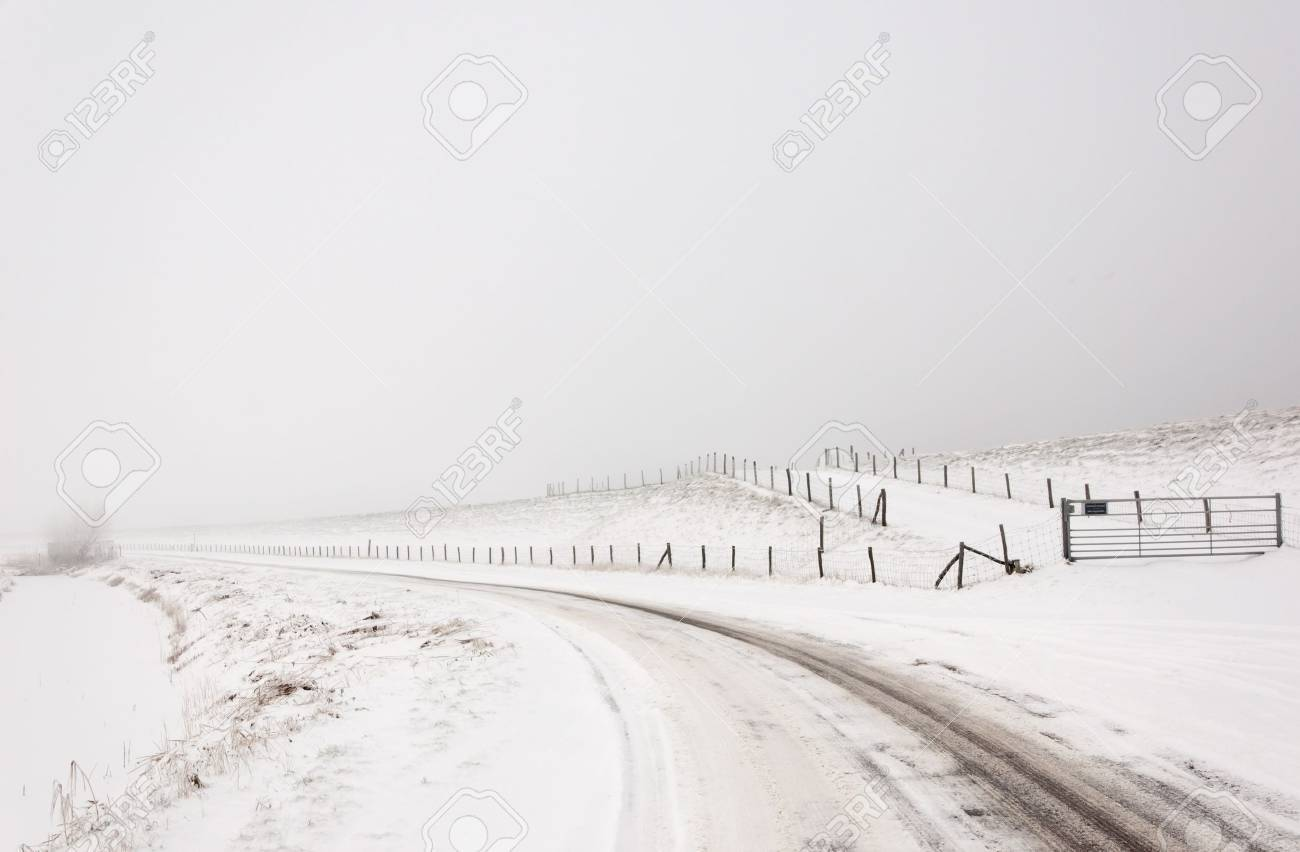 A snowy landscape with a road, fences and a dike. It is very early in the morning and it freezes very much in the Netherlands. The morning mist still hangs over the landscape. The view is limited and less colorful. Stock Photo - 12307231