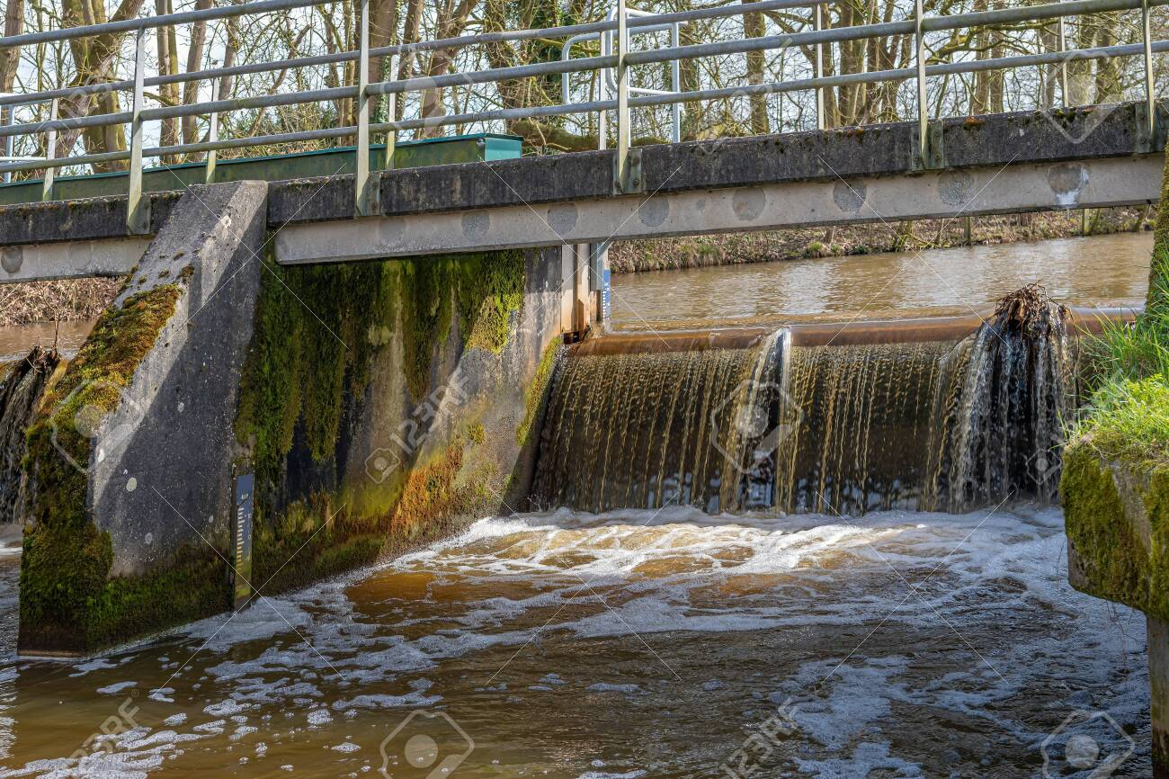Water in a narrow Dutch river flows over the weir under the bridge. There is a water level meter on both sides of the weir on the wall. - 137897011