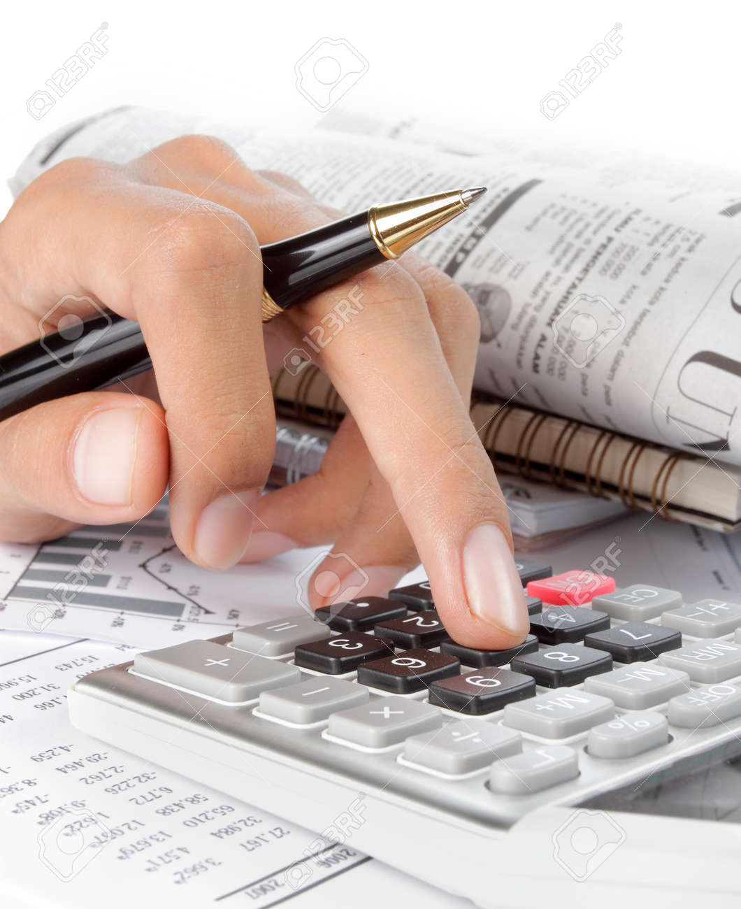 woman's hands with a calculator and a pen. newspaper on a background Standard-Bild - 9469681