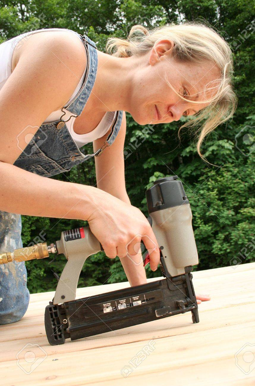 An attractive girl shows off her handywoman skills by nailing on new cedar decking. Stock Photo - 440146