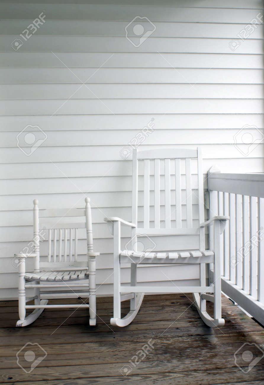 Ein Erwachsener Und Kinder Der Stühle Auf Einer Veranda Schaukeln.  Standard Bild   1353026