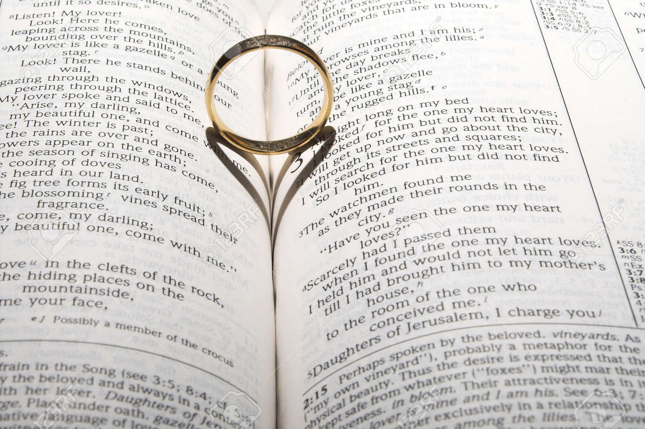 A Wedding Ring On A Bible Open To Marriage Scripture Stock Photo