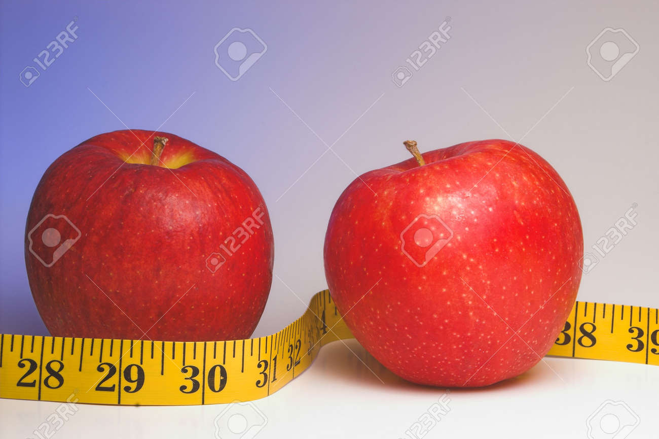Two red apples wrapped in a tailor's measuring tape. Stock Photo - 2691707