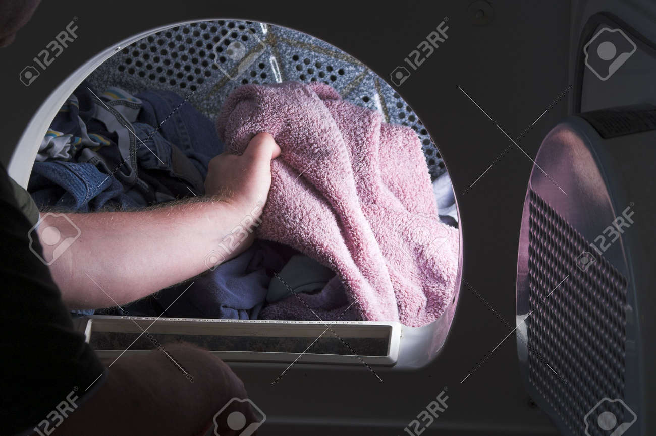 A man taking laundry out of a clothes dryer. Stock Photo - 2933172