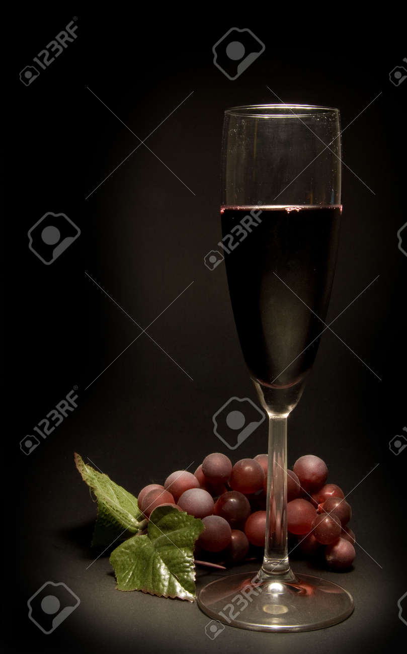 A glass of red wine and a bunch of grapes. Stock Photo - 4020917
