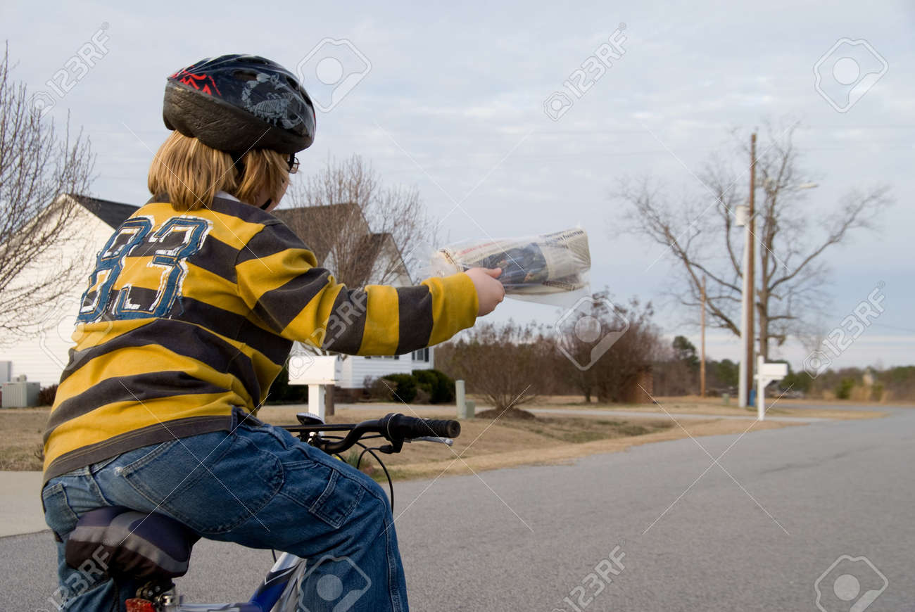 A boy delivering newspapers on his bicycle. - 4310053