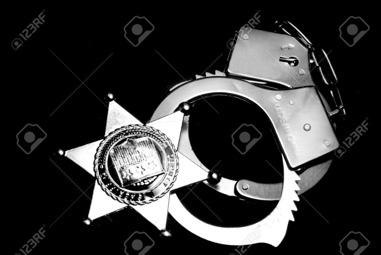 A sheriffs badge and a pair of handcuffs Stock Photo - 6245423