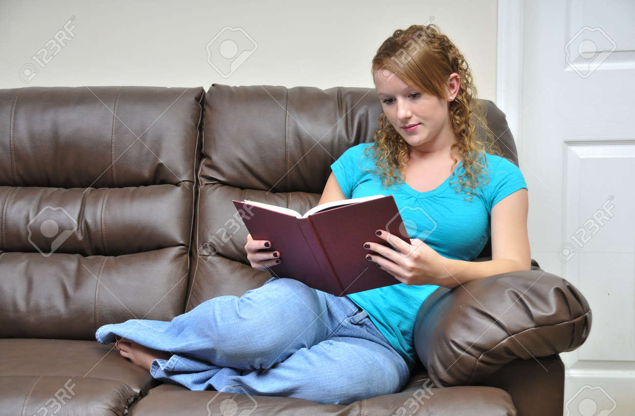 0aba8722569f A woman reading a book on a couch Stock Photo - 7383748