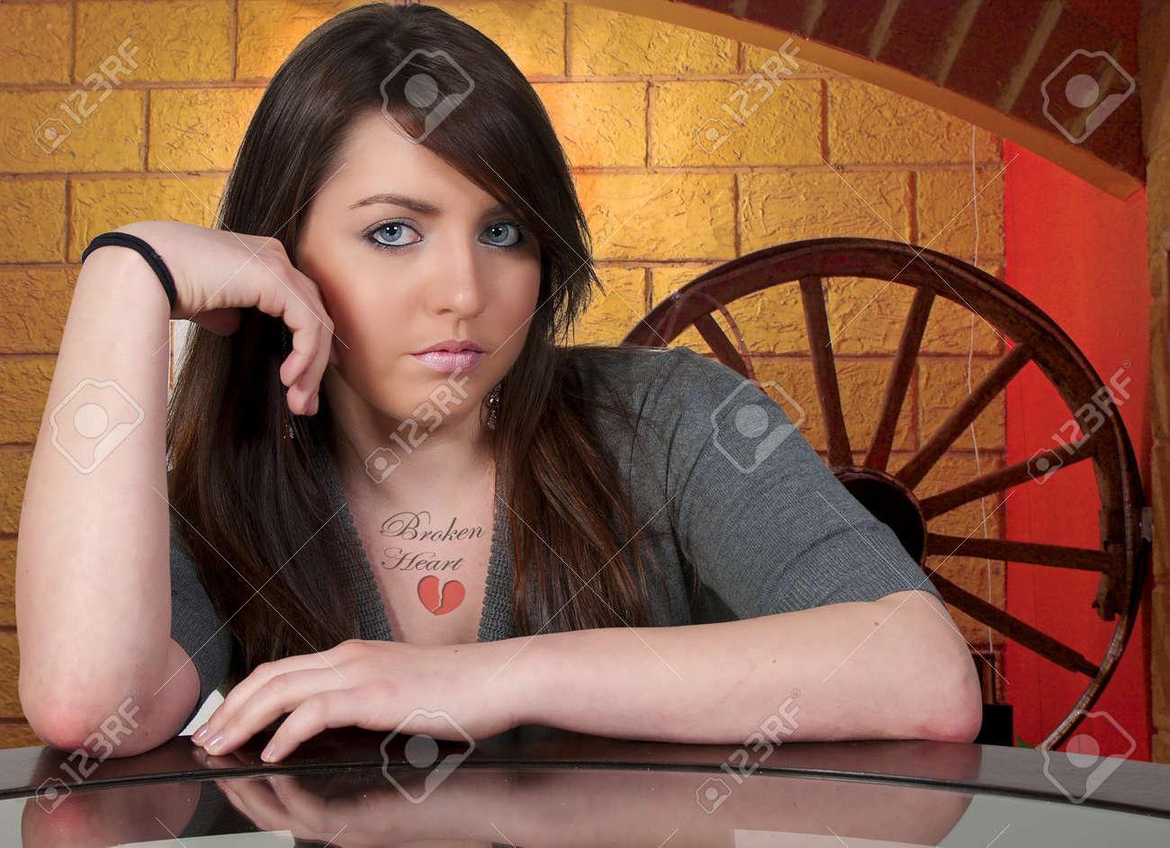 Une Belle Jeune Femme Avec Un Tatouage Qui Dit Coeur Brise Banque D
