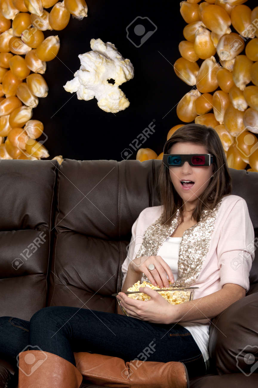 Beautiful young woman watching a 3d dvd movie on tv at home Stock Photo - 8890917