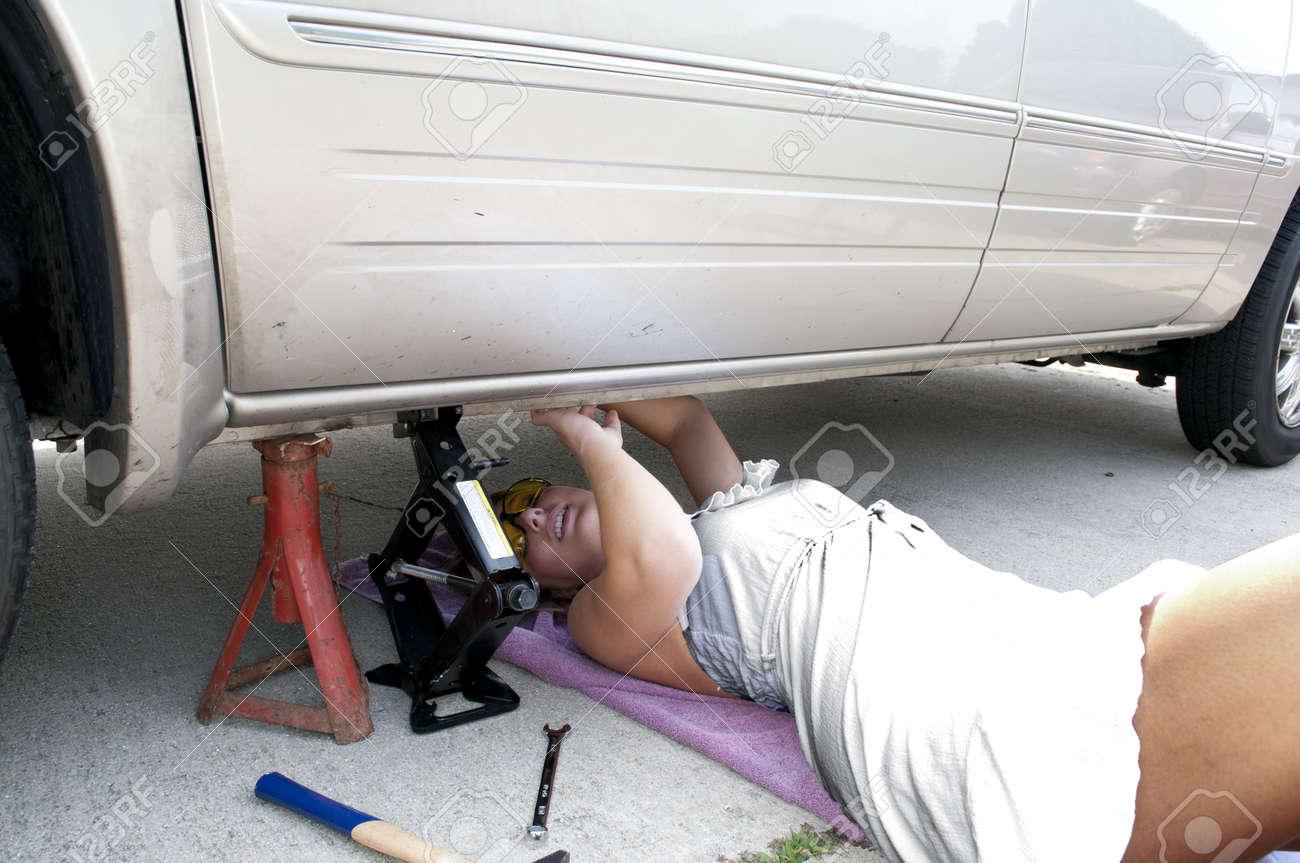 A beautiful female mechanic working on an automobile Stock Photo - 10196313