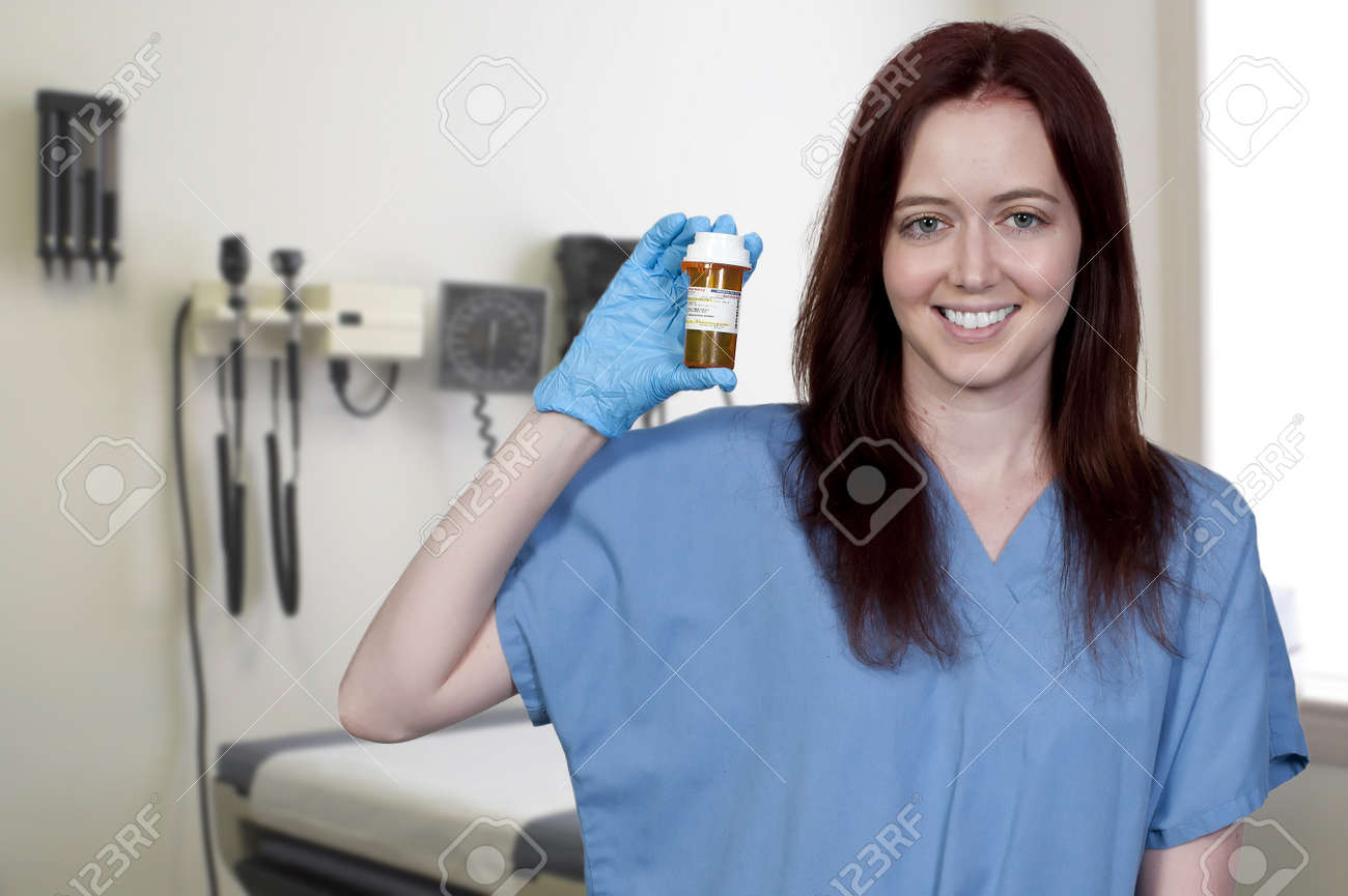 A beautiful young female doctor on her rounds holding a prescription bottle of medicine pills Stock Photo - 10197629