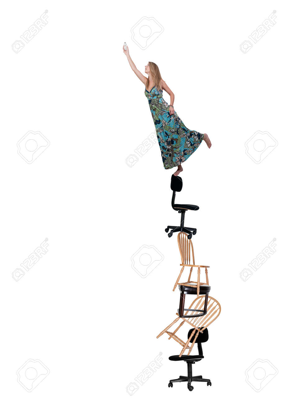 A Woman Standing On Chairs And Stools To Change Light Bulb Stock Wiring Photo