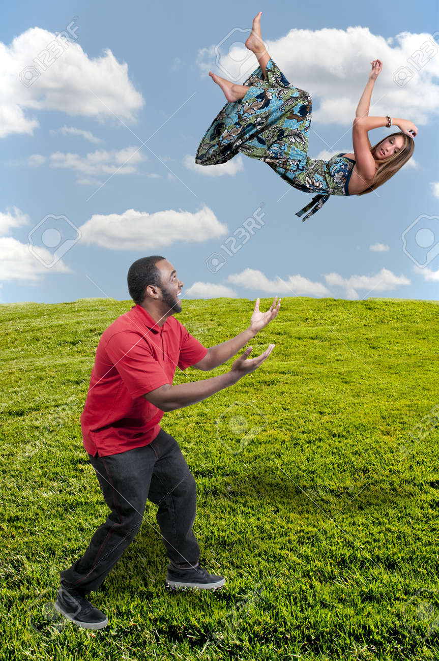 Handsome man catching a beautiful young woman falling through the sky Stock Photo - 13933954