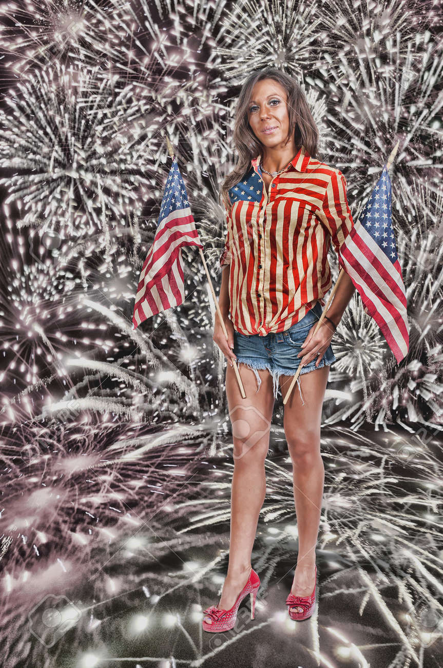 Beautiful woman holding a US flag at a fireworks display Stock Photo - 21912902