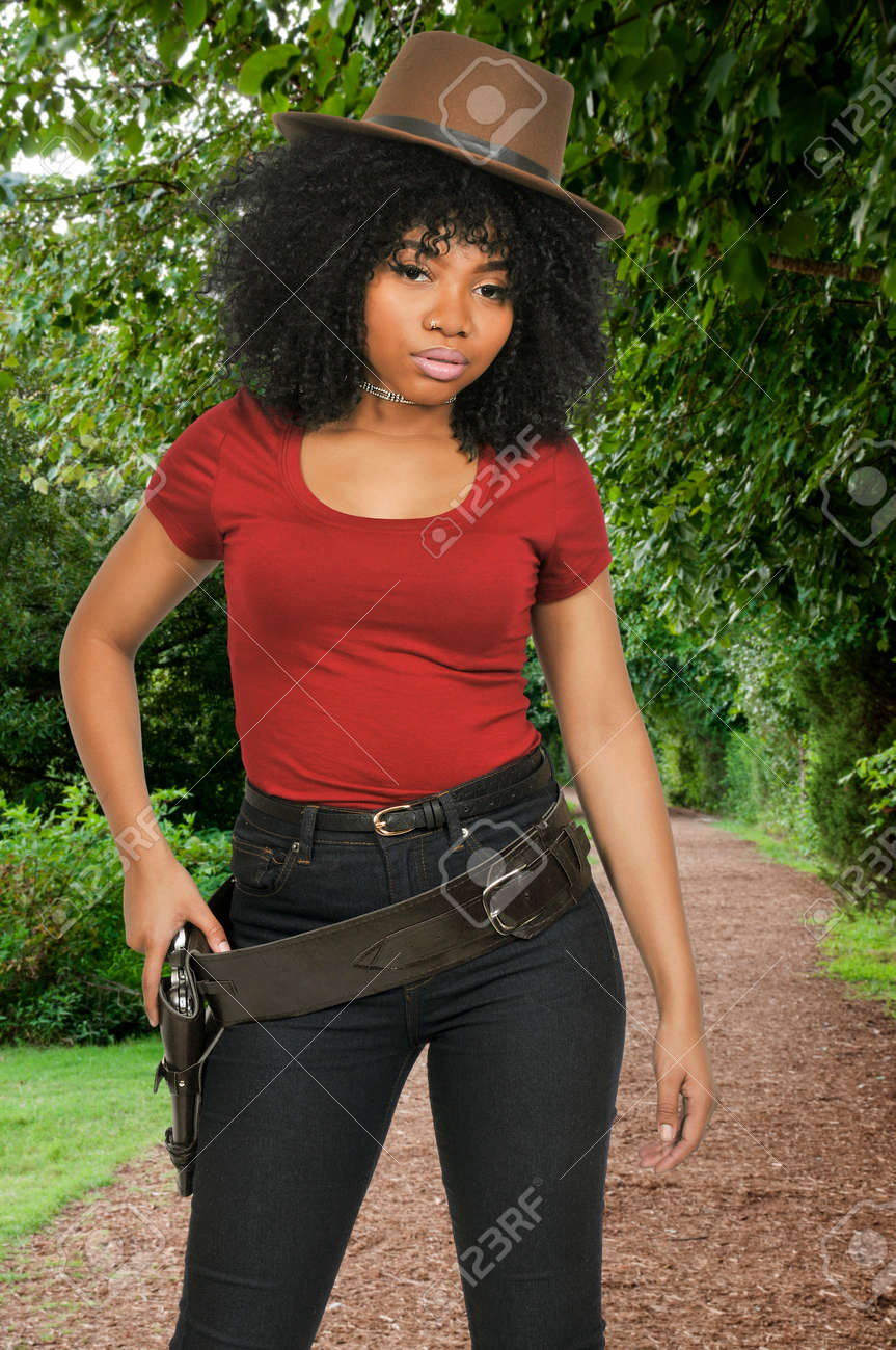 Beautiful young country girl African American black woman wearing a cowboy  hat and revolver Stock Photo 7e08a121f68