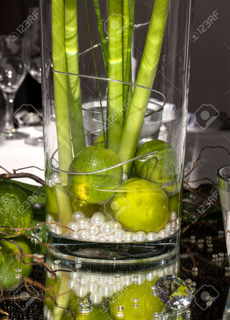 Festive table decoration with limes and plant stems in a large festive table decoration with limes and plant stems in a large glass vase designed on floridaeventfo Image collections