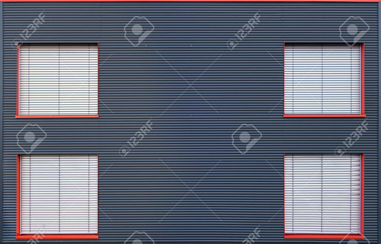 Four With Gray Blinds Closed Windows With Red Frames In The Facade Of On Industrial