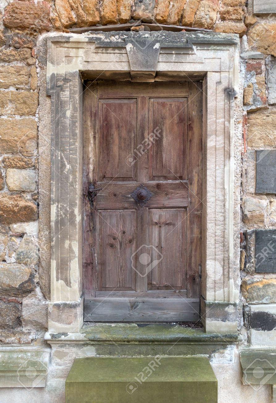 Vieux Portail En Bois vieux, brun, tanné porte en bois avec poignée de porte ancienne et poignée  centrée en métal dans un portail en pierre. devant ya deux étapes.