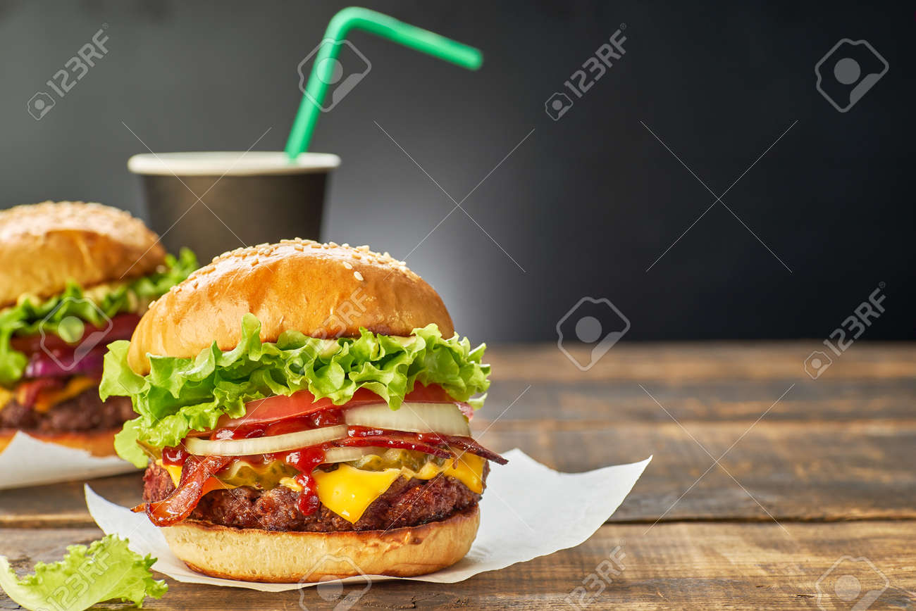 Two hamburgers and cup of drink served on dark wooden table - 139622539