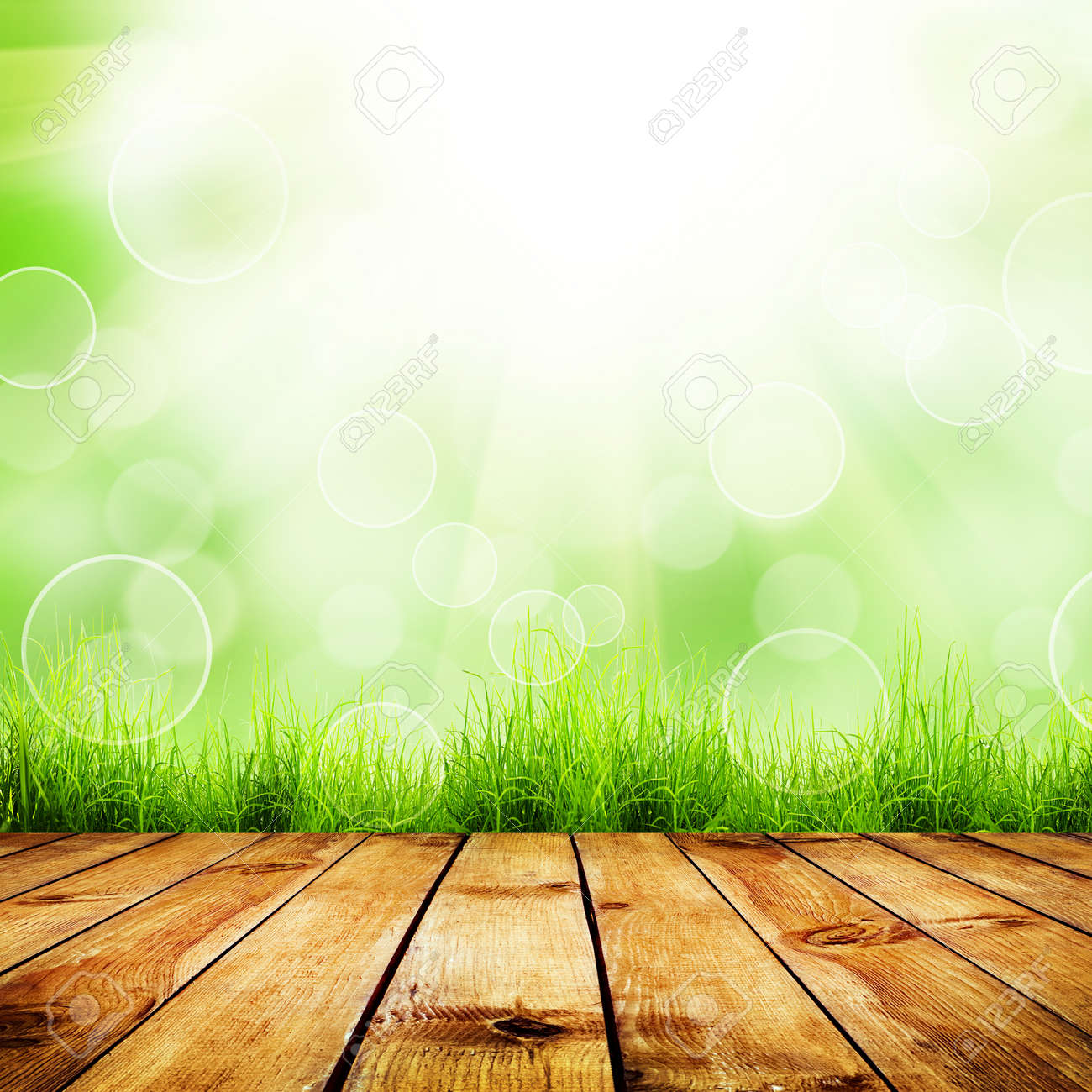 Fresh spring green grass with green bokeh and sunlight and wood floor. Natural background - 34128640