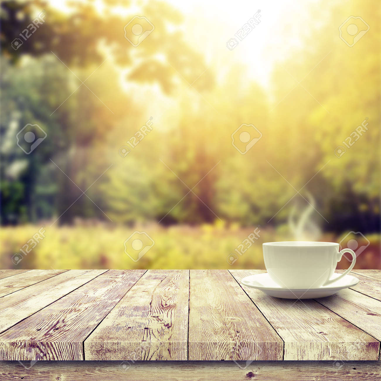 Plain wood table with hipster brick wall background stock photo - Cup With Hot Drink On Wood Table Over Forest Background