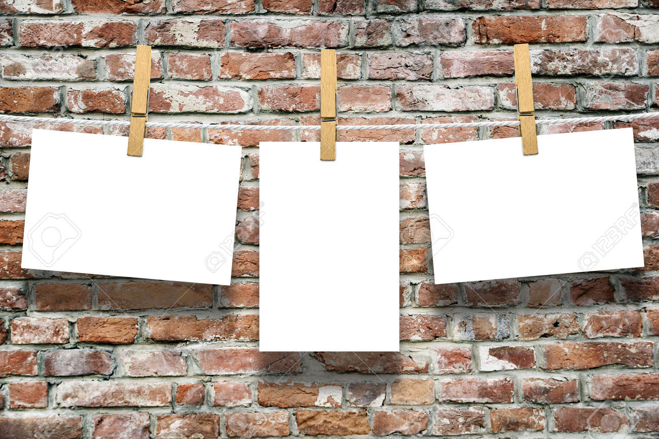 Photo Frames With Pins On Rope Over Old Aged Brick Wall Background