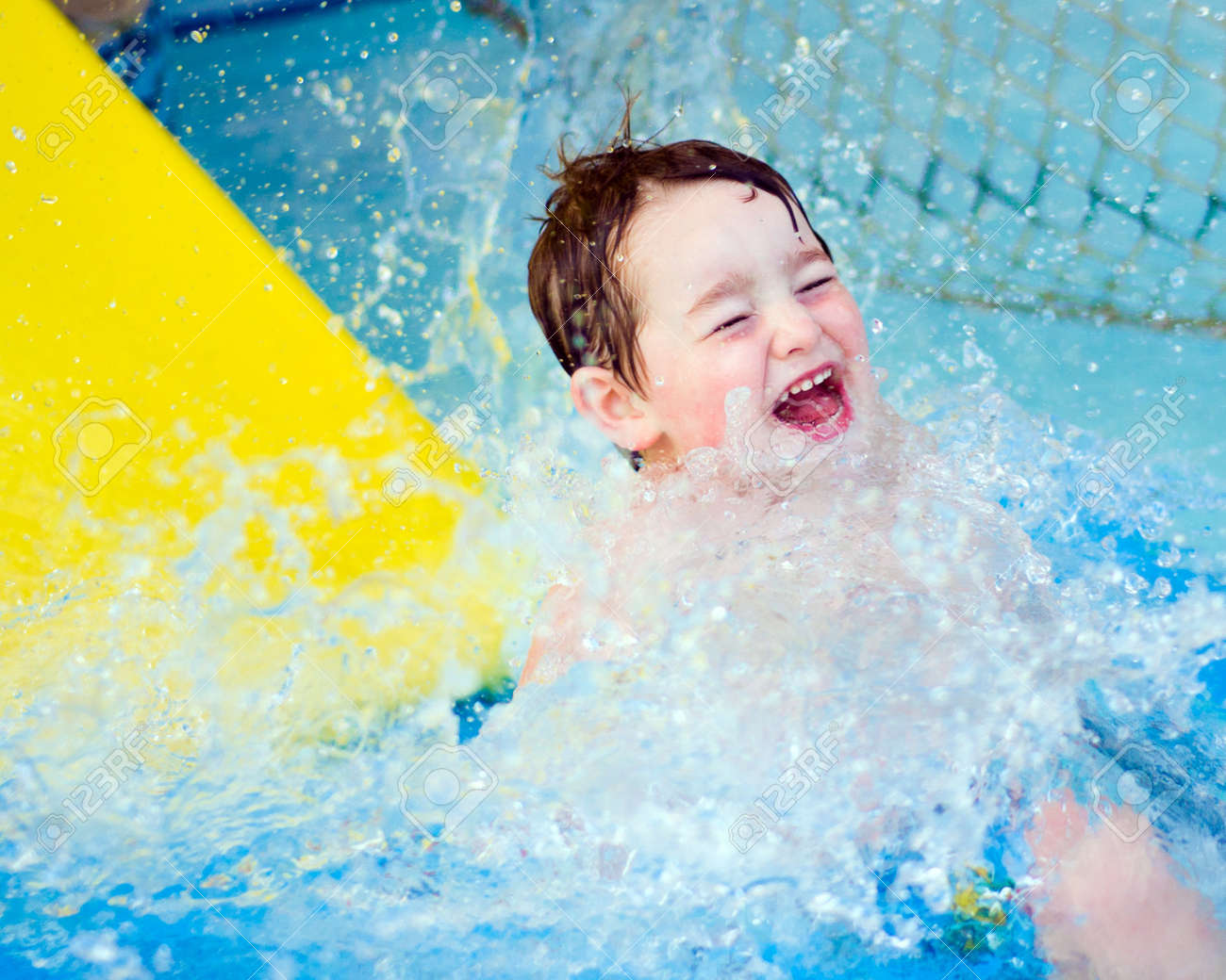 Boy splashes down after riding water slide Stock Photo - 9748689
