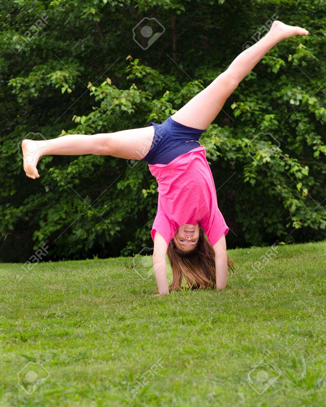 Young girl doing a cartwheel outdoors at park Stock Photo - 13387633
