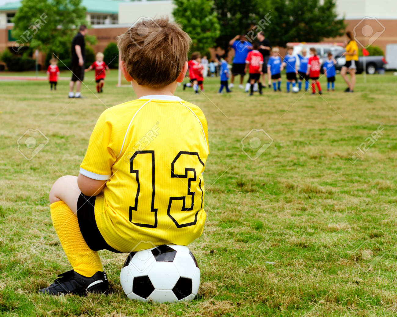Young boy child in uniform watching organized youth soccer or