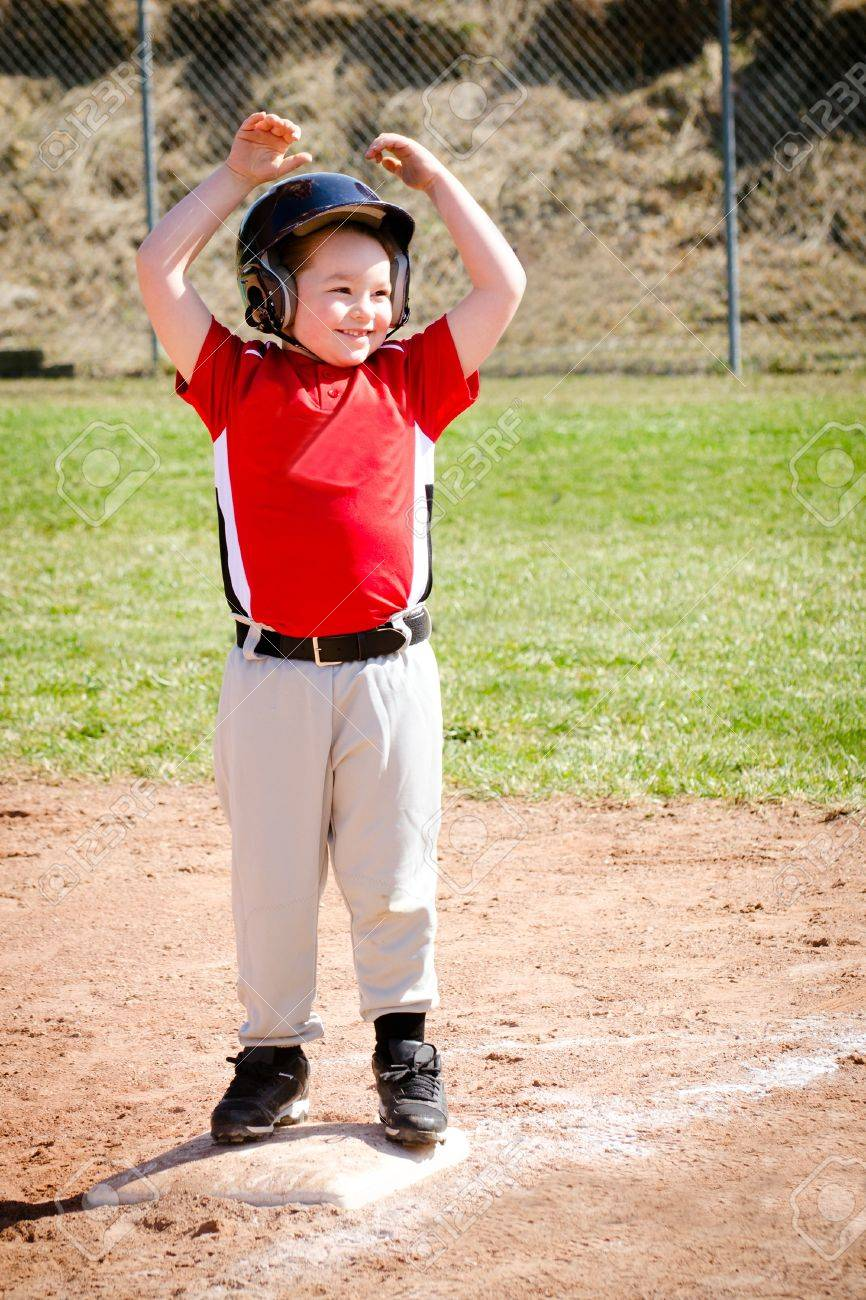 Child celebrates on base after making a hit during baseball game Stock Photo - 18347300