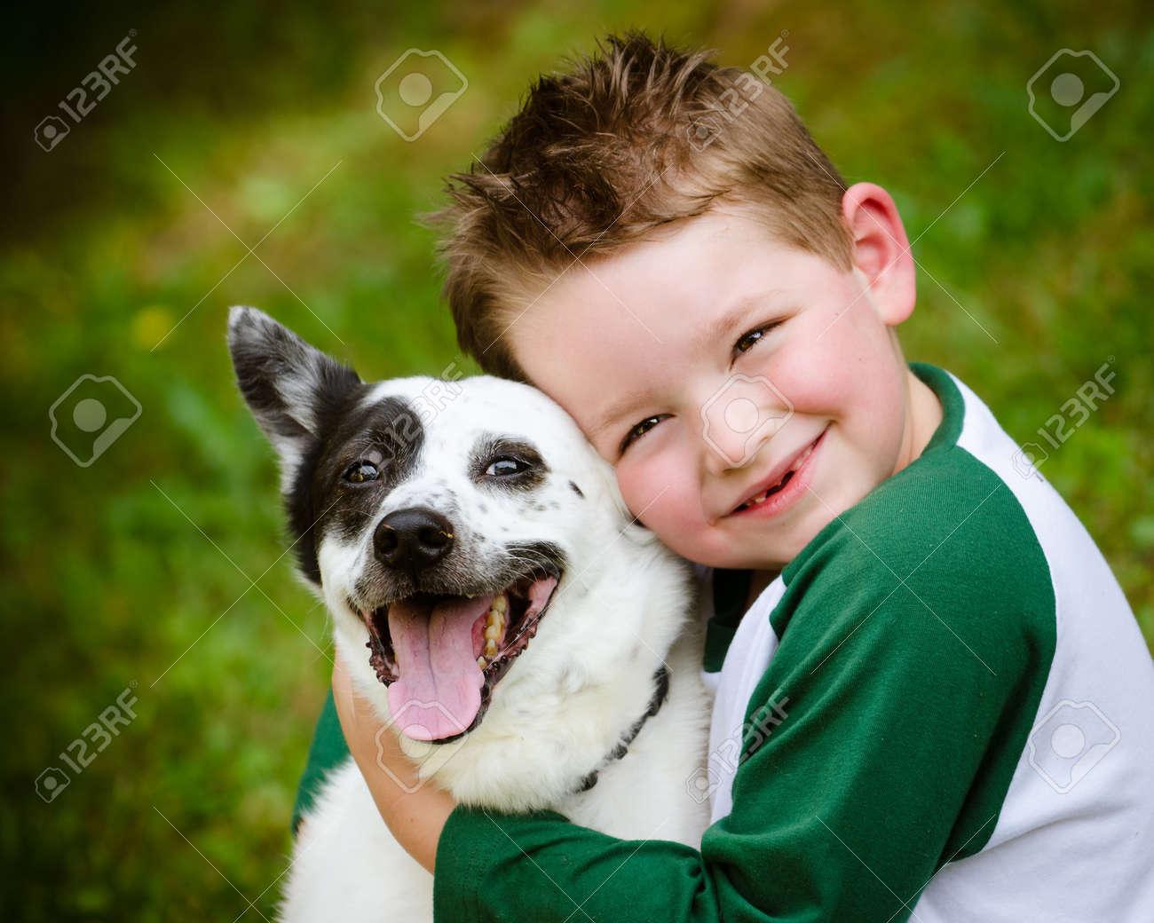 Child lovingly embraces his pet dog, a blue heeler - 19638411