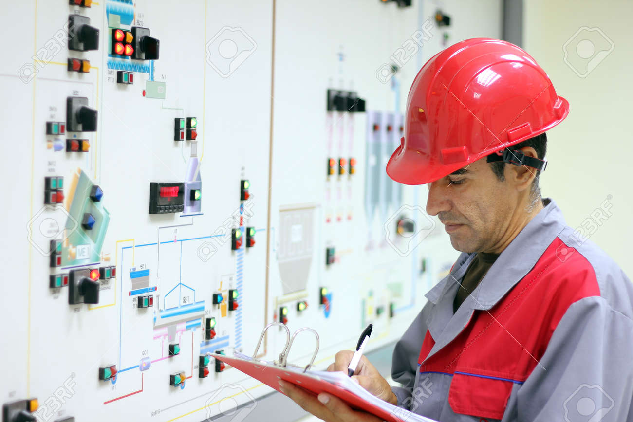 Engineer standing in front of the control panel in the control room and write the results of the measurements. Stock Photo - 7884451