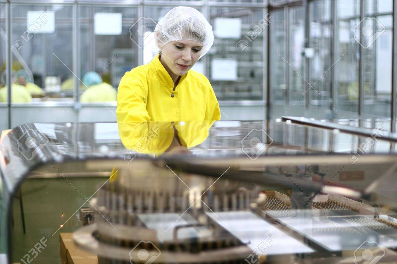 Lab technician working inside a pharmaceutical factory. - 9434495