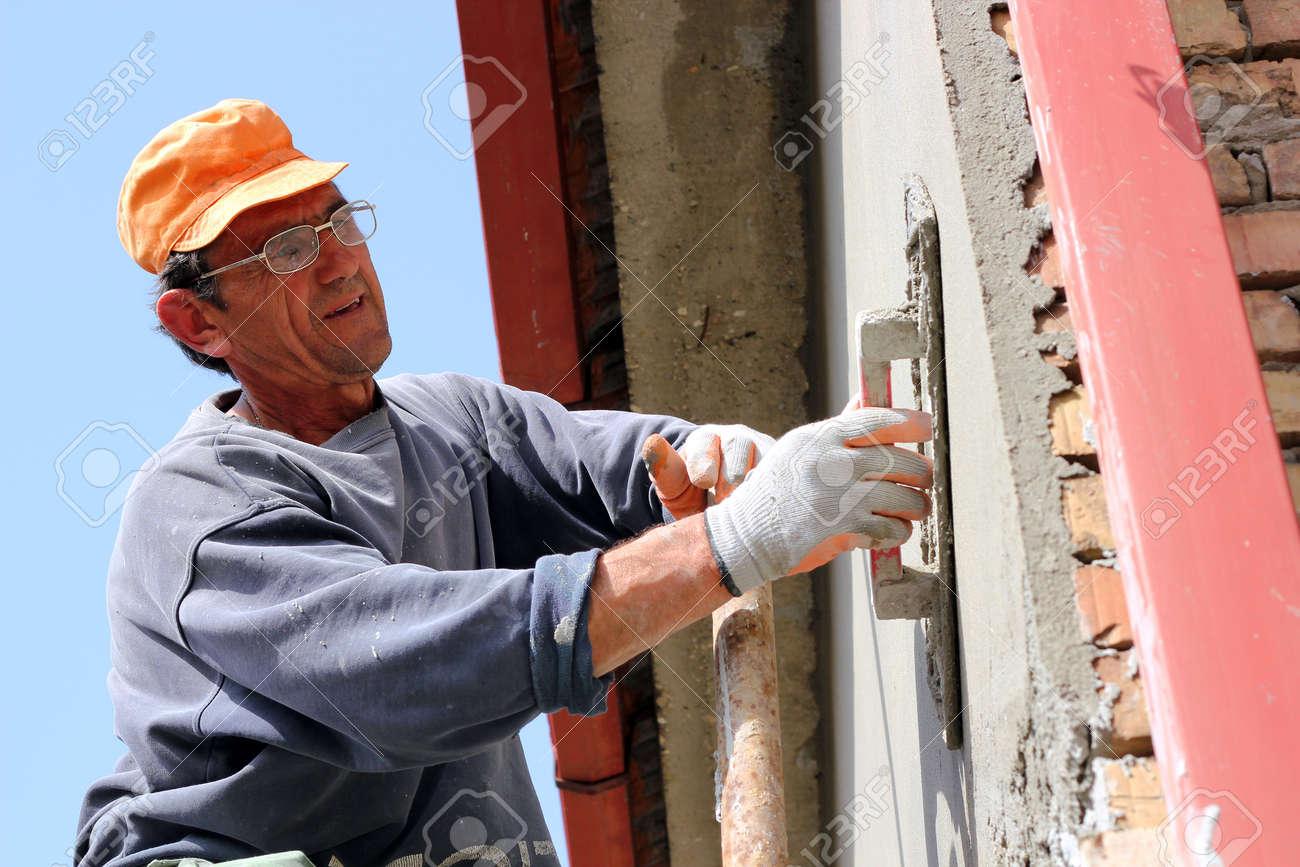 Mature contractor plasterer working outdoors - 13116036