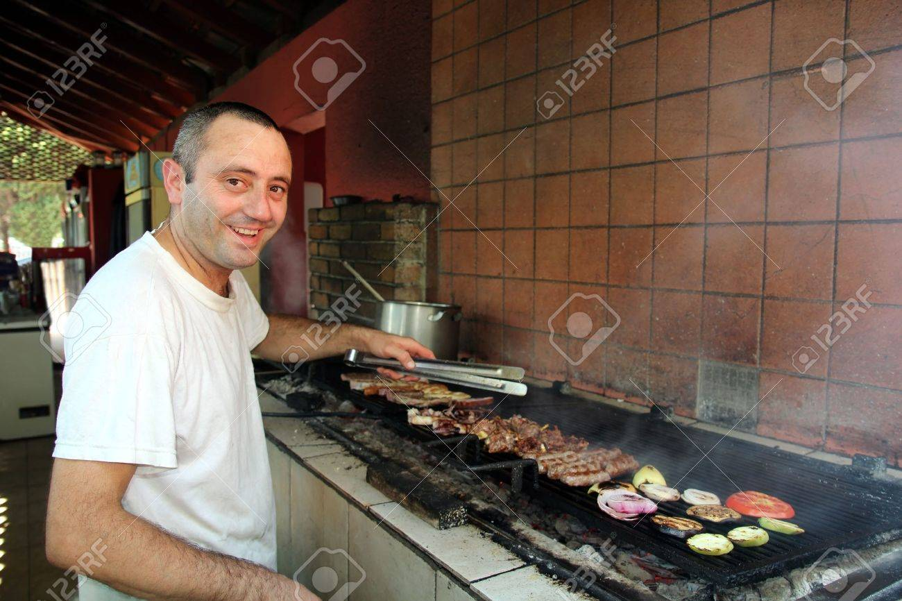 Smiling Chef Grilling Meat In Outdoor Commercial Kitchen Selective ...