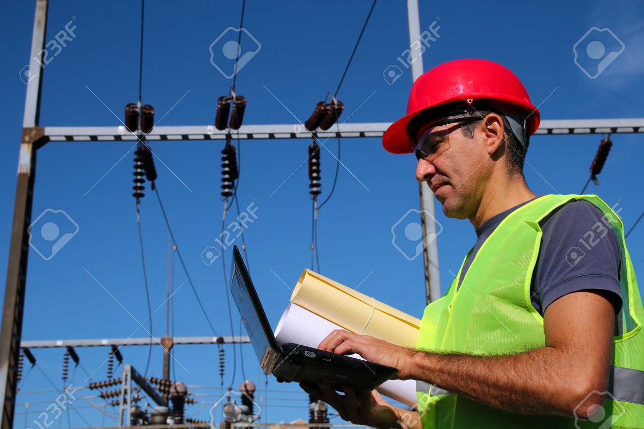 Electrical Engineer With Laptop and Blueprints - 16307757