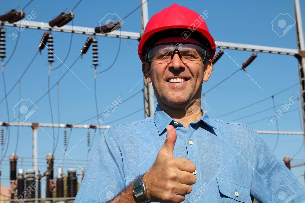 Thumb up given by smiling engineer next to electrical substation - 25524012
