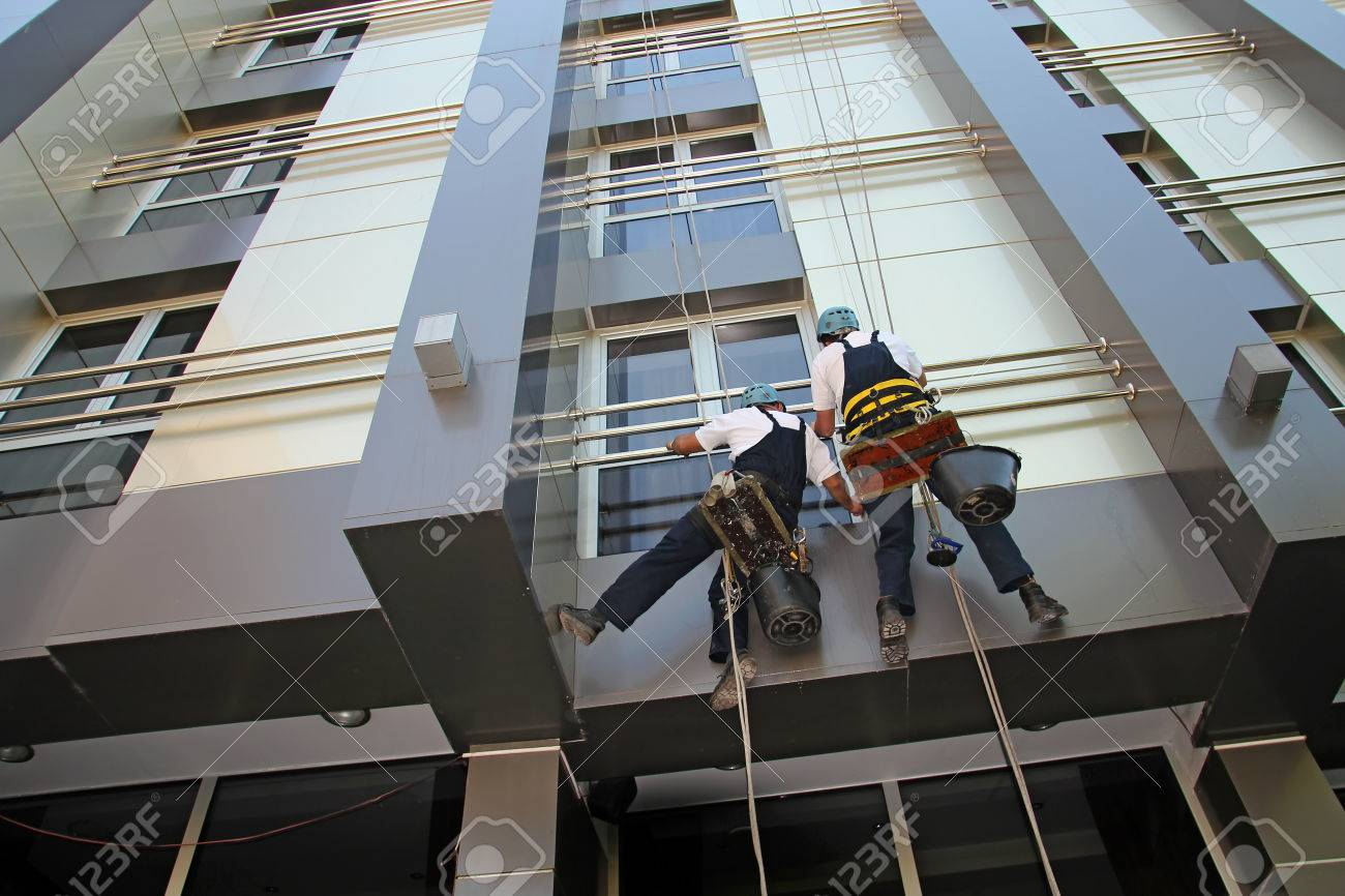 Industrial Climbers Washing Facade of a Modern Building - 33058763