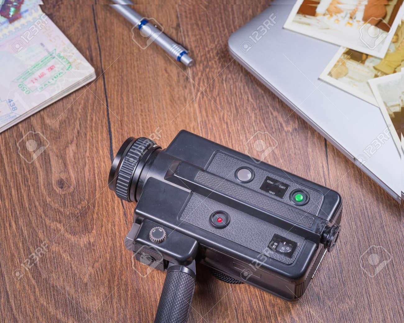 8Mm Vintage Camera vintage image with old black video camera 8mm,old photo,laptop,pen..