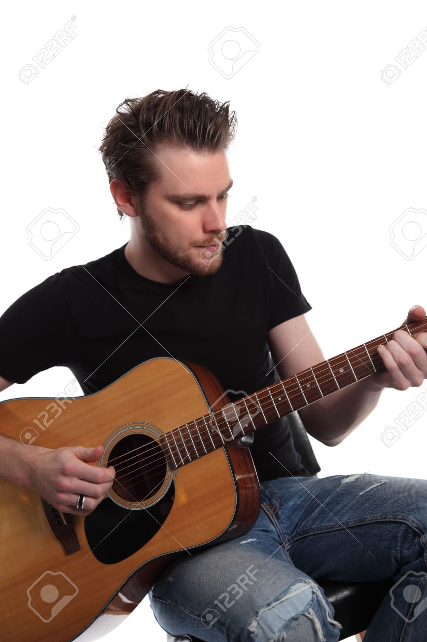 Young singer songwriter. Sitting down with an acoustic guitar, wearing a black t-shirt with torn jeans. White background. Stock Photo - 17342239