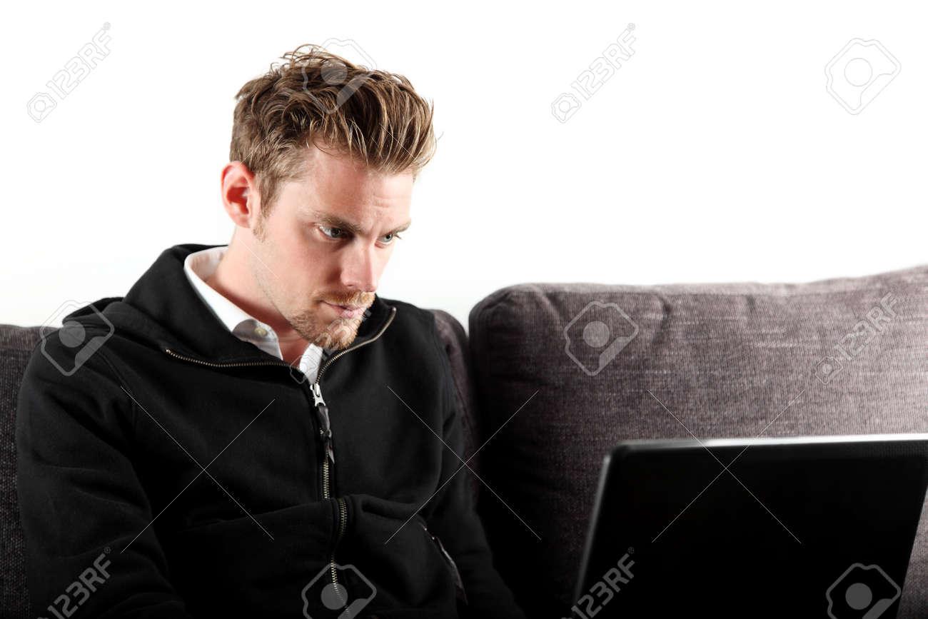 17098faf5304 Hombre joven y atractiva, que llevaba una sudadera con capucha y jeans  negro, con un ordenador portátil en su regazo. Sentado en un sofá. Fondo ...